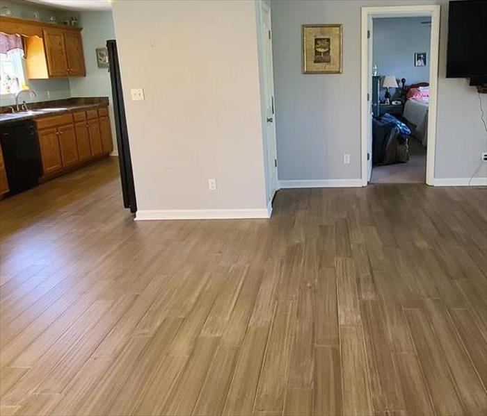 Picture is of Living Room and Kitchen Flooring after Water Restoration Process