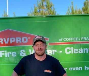 A male SERVPRO employee standing in front of a SERVPRO vehicle for a photo