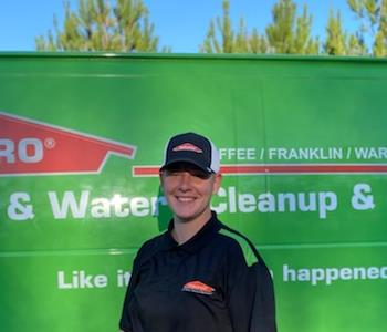 A female SERVPRO employee standing in front of a SERVPRO vehicle for photo