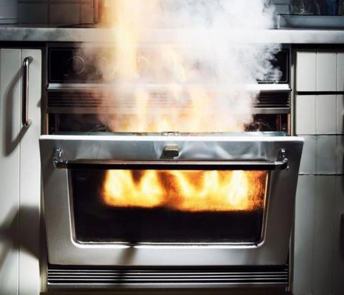 An open kitchen oven with flames shooting out of the opening.